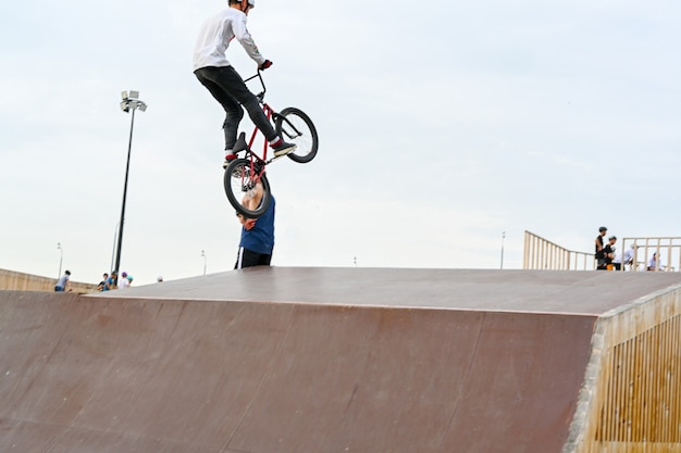 The cyclist rides in an extreme park. the stuntman. the skate park, rollerdrome, quarter and half pipe ramps. extreme sport, youth urban culture for teen street activity.