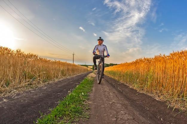 사이클 선수는 밝고 화창한 날에 필드에서 도로를 타고. 스포츠와 취미. 야외 활동