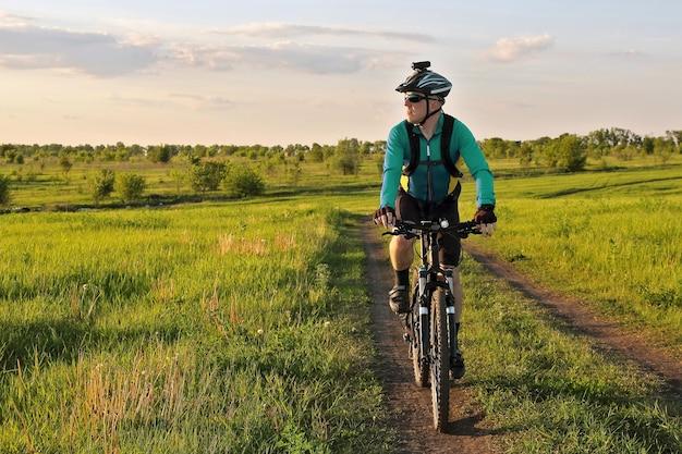 밝고 화창한 날에 필드에서 도로에 자전거 타기