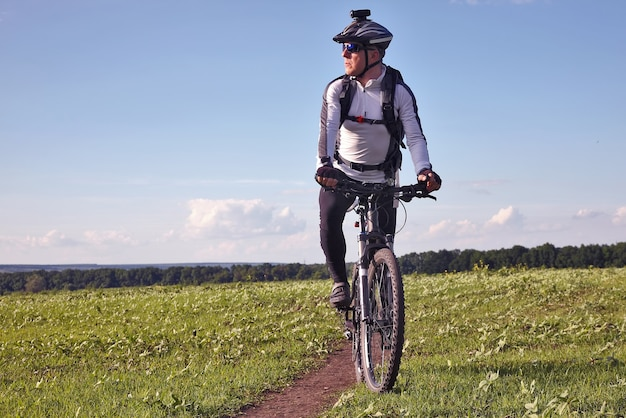 Cyclist rides on the road in a field on a bright sunny day