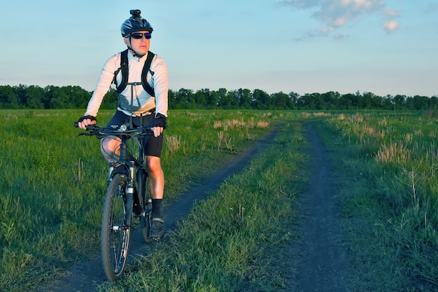 Cyclist rides on the road in the field