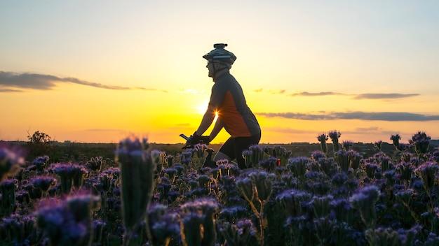 자전거 타는 사람은 화창한 일몰을 배경으로 꽃밭을 타고