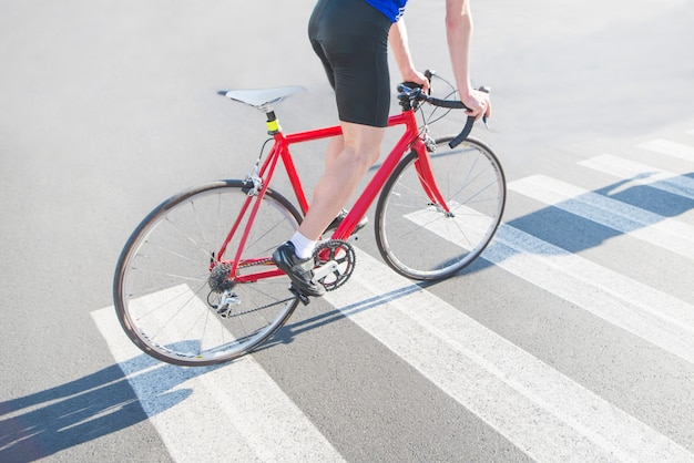 Cyclist rides a zebra on a red road bike
