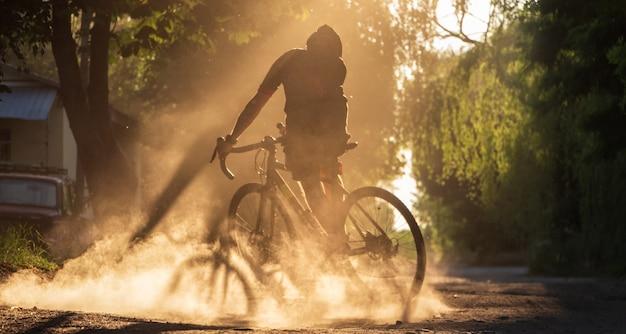 日没時に砂利道で自転車に乗るサイクリスト。ほこりの雲の中で砂利自転車に乗って若いスポーティな男のシルエット。