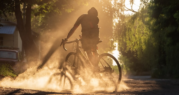 Cyclist riding a bicycle on a gravel road at sunset. a silhouette of young sporty man on a gravel bike in a cloud of dust.