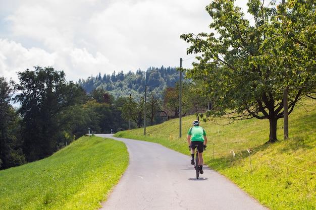 Cyclist riding a bike along a mountain asphalt road