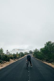 Ciclista in sella a una bicicletta al tramonto in una strada di montagna
