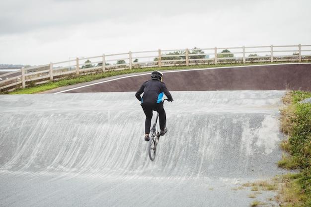 Велосипедист езда на велосипеде bmx в скейтпарк