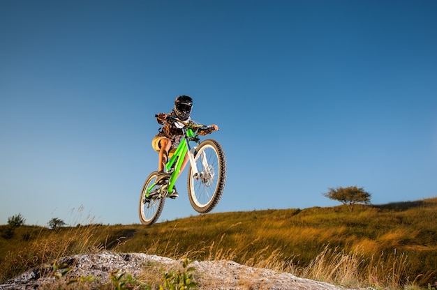 Велосипедист катается на горном велосипеде вниз по склону