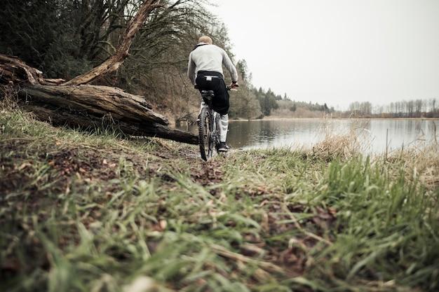Cyclist riding mountain bike toward lake