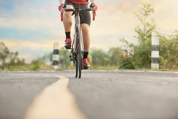 Cyclist  in a road outdoors at sunset time