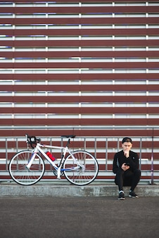 Cyclist sits on the background of the wall and uses a smartphone. copyspace