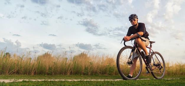 サイクリストは、ゴールデンアワーに畑の自転車に乗っています。アクティブなライフスタイルのコンセプト。スペースをコピーします。