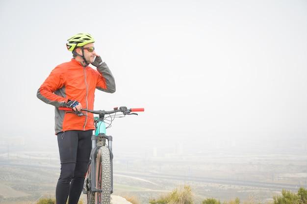 Велосипедист разговаривает по мобильному рядом со своим велосипедом