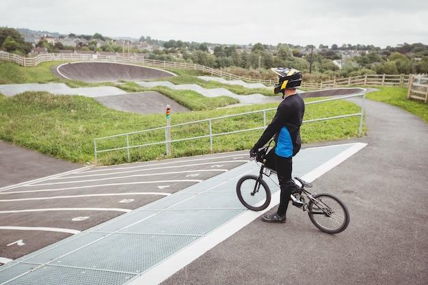 Велосипедист стоит с велосипедом bmx на стартовой рампе