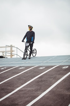 Cyclist standing with bmx bike at starting ramp