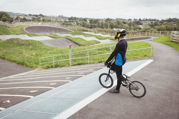 Cyclist standing with bmx bike on starting ramp