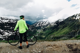 Cyclist standing with road bikes on background of beautiful Alpine mountains landscape