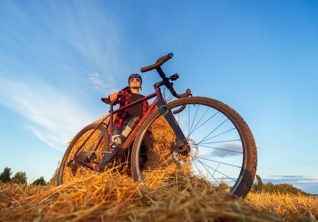 サイクリストは、自転車を持って壮大な夕日を楽しんでいる畑の干し草の山のそばに立っています。