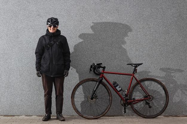 サイクリストは自転車でコンクリートの壁の近くに立っています