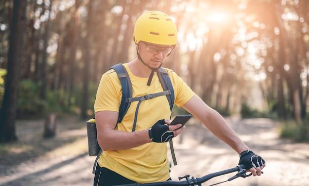 Велосипедист с помощью gps-навигатора на смартфоне в солнечном лесу