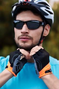 그의 스포츠 헬멧을 착용하는 사이클