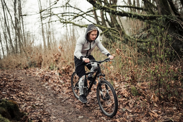 Cyclist wearing hooded top riding bicycle in the forest