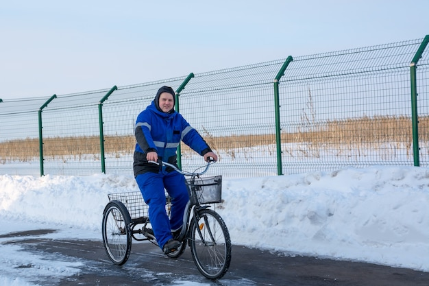 Cyclist in winter on a tricycle on a background of snowy hills, snowdrifts, fences and asphalt.