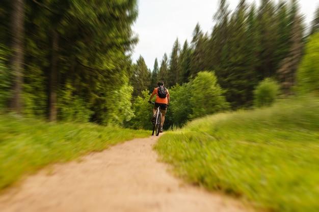 산악 자전거에 배낭을 메고 숲길을 따라 타는 자전거 타는 사람