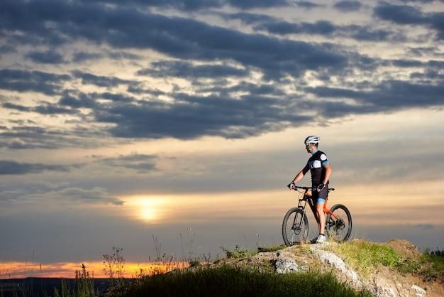 Велосипедист с велосипедом отдыхает на вершине скалы в горах, наслаждаясь солнцем на закате под необычным небом с красивыми облаками