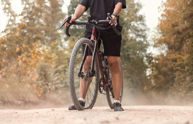 ほこりっぽい田舎道で砂利自転車を持ったサイクリスト。アクティブなライフスタイルのコンセプト。