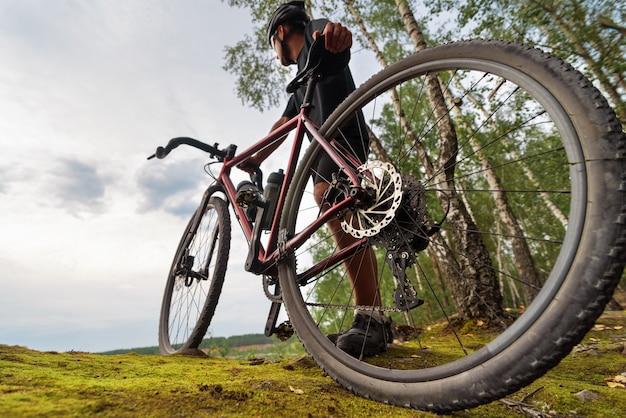 トレーニング後にリラックスしながら美しい景色を楽しむグラベルバイクを持ったサイクリスト。ローアングルビュー。 Premium写真
