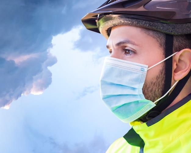 医療用マスクを持つサイクリスト、地平線を見て、covid-19による検疫のスポーツ