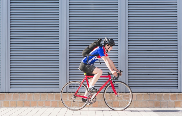 Cyclist with a backpack rides on a road bike on a gray wall