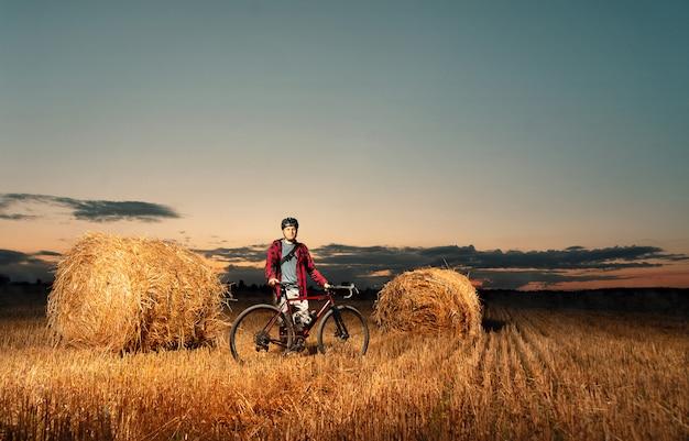 夕暮れ時のわら俵とフィールドに立っている自転車のサイクリスト。
