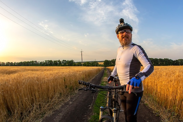 The cyclist with the bike in a field watching the sunset. sports and hobbies. outdoor activities