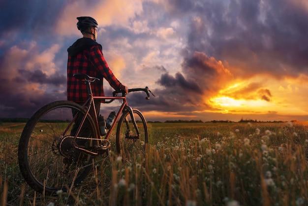ゴールデンアワーの間に劇的な夕日の空を見ているフィールドで自転車とサイクリスト。