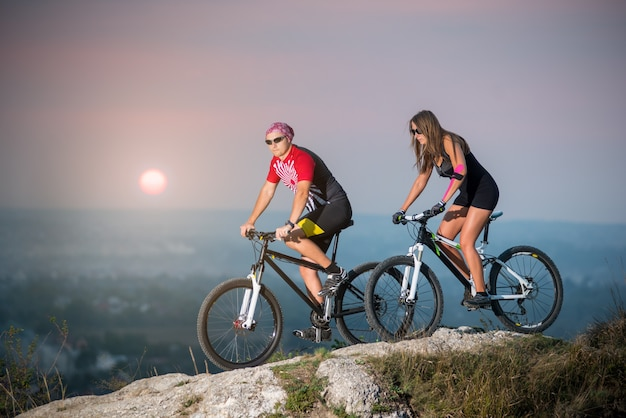 Cyclist with girlfriend riding on sports bicycles at sunset