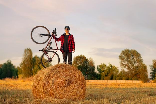 Велосипедист с гравийным велосипедом стоит на вершине стога сена в поле на закате.