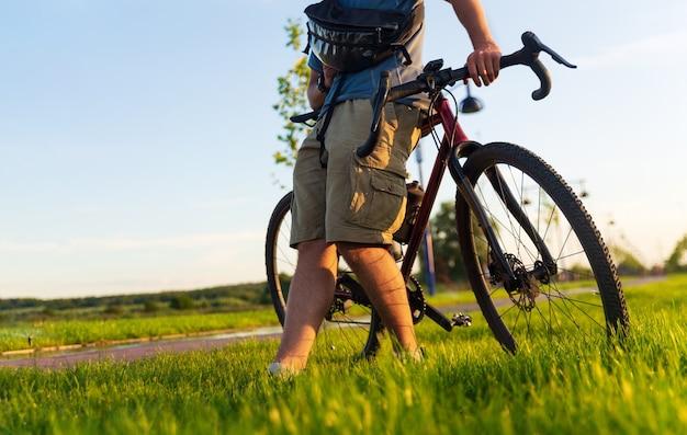 日没時に公園の緑の芝生の上に立っている砂利自転車とサイクリスト。スポーツとアクティブなライフスタイルのコンセプト。