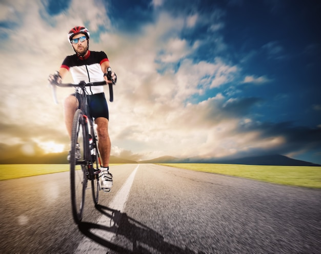 Cyclist with helmet pedaling faster on road