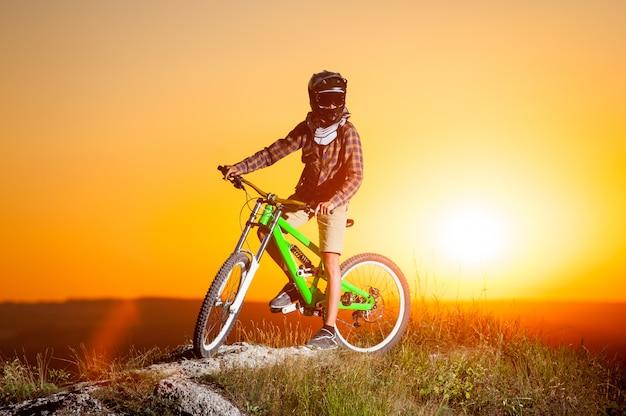 Велосипедист с горным велосипедом на холме вечером