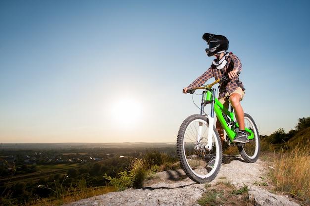 Велосипедист с горным велосипедом на холме под голубым небом