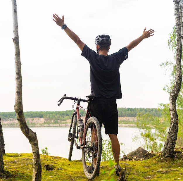 Cyclist with raised arms in a helmet stands at a cliff above the lake.