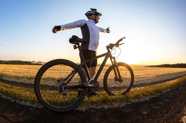 팔을 들고 있는 자전거 타는 사람은 들판의 석양을 배경으로 자전거 근처에 서 있다