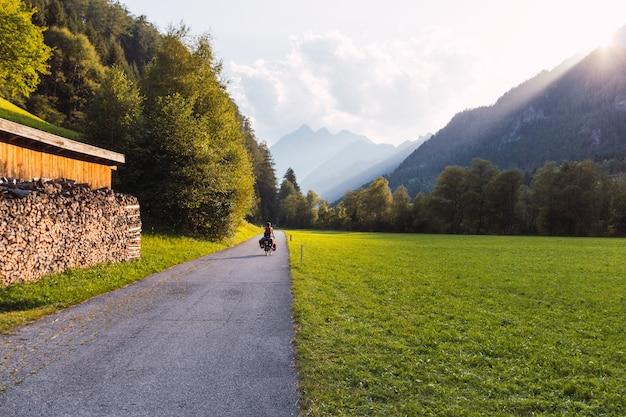 山々と山々の間の太陽の光が降り注ぐオーストリアアルプスの自転車道をサドルバッグで漕ぐサイクリスト