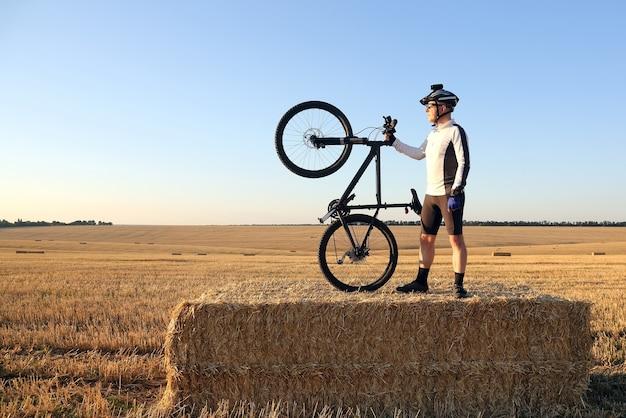 Велосипедист с велосипедом на поле, собранном из соломы