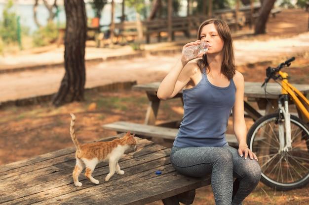 Велосипедистка пьет воду рядом с велосипедом в общественном парке с бездомной кошкой