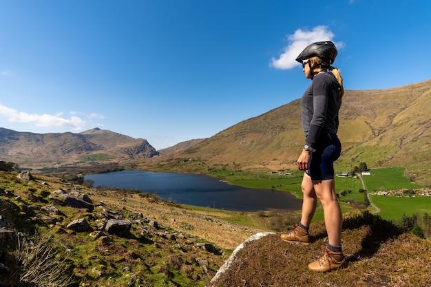 Велосипедист женщина смотрит на горный пейзаж