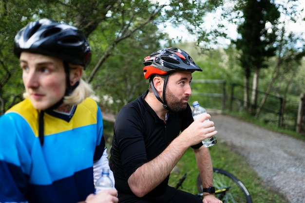 Cyclists resting and drinking water in the forest